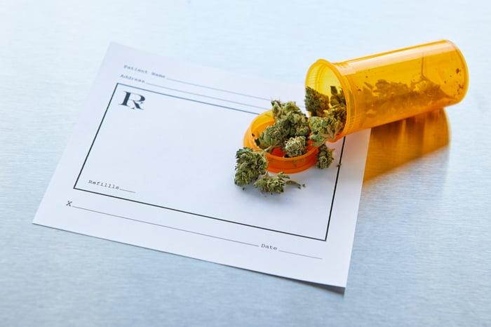 Marijuana buds spill out of a prescription bottle onto a prescription.