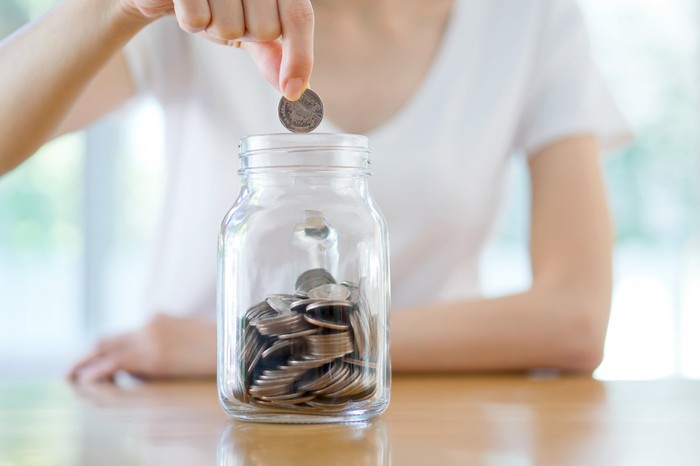 Woman dropping coin into glass jar that's half-filled with coins