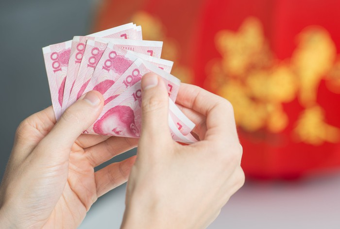 Hands counting Chinese yuan notes