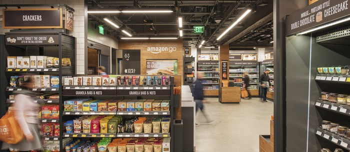 The inside of an Amazon Go store with shoppers choosing from snack and drink options.