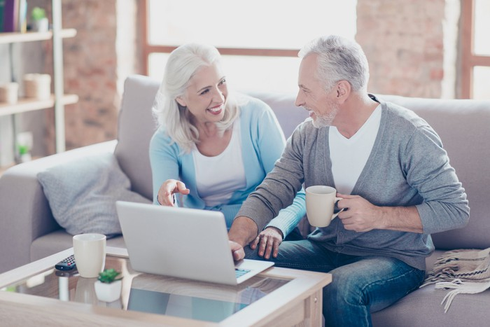 Smiling senior man and woman sitting on couch, facing each other while man's hand hovers over laptop on coffee table