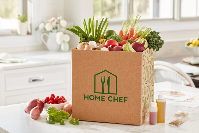Vegetables inside a Home Chef box on a kitchen table