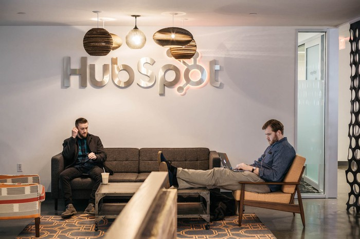 Two men sitting in front of a HubSpot sign.