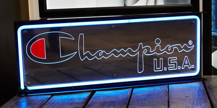A store display with the Champion logo brightly lit in a blue neon light.