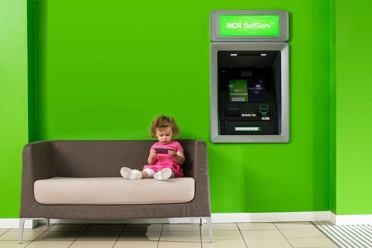 Child sitting on a couch in front of an NCR ATM.