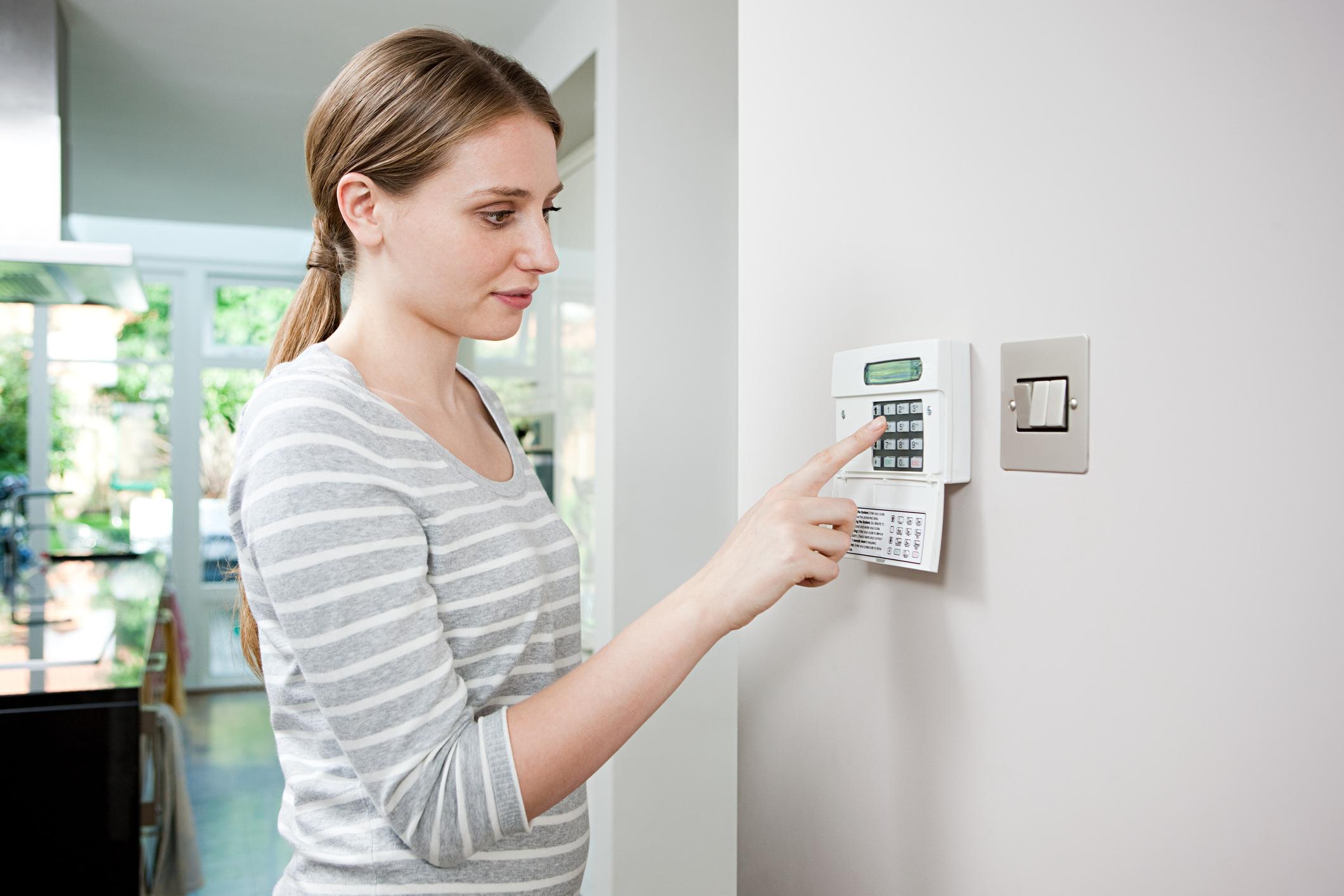 A woman setting a security alarm.