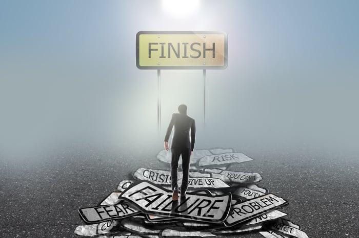 A businessman climbing a mountain of failure signs toward a finish line.