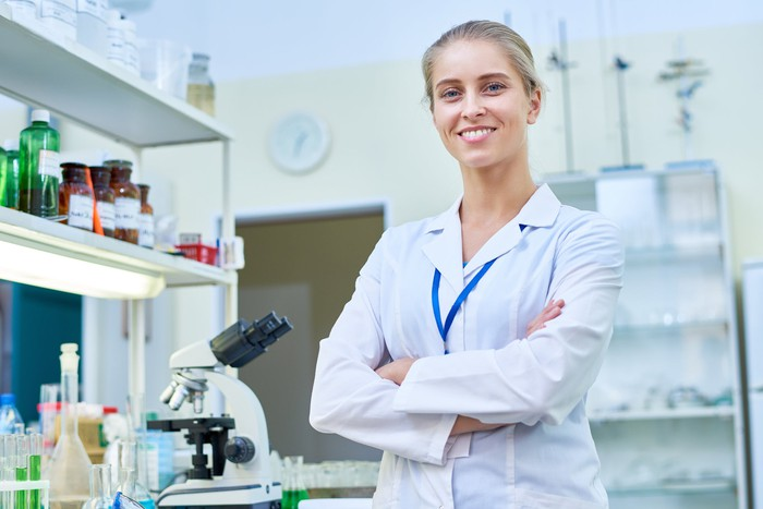 A smiling woman in lab coat in a lab with arms crossed.