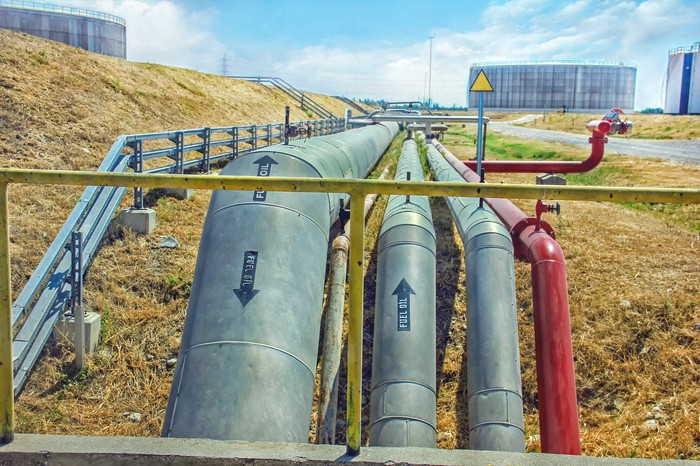 Several pipelines with storage tanks in the background.