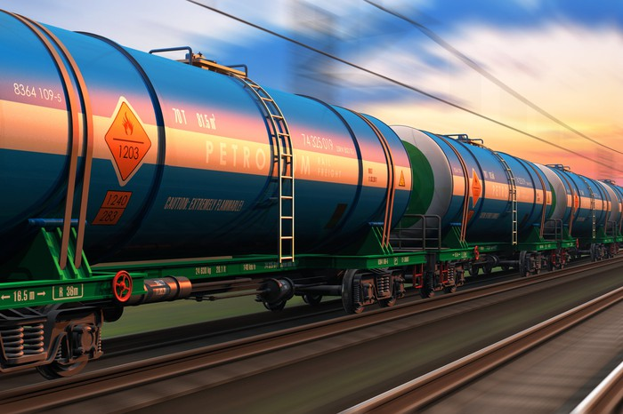 A freight train with tanker cars at sunset.