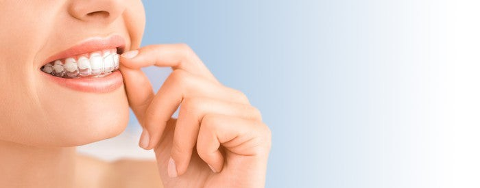Woman touching her clear plastic dental retainer.