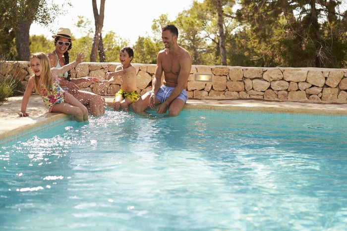 Family of four sitting by a swimming pool.
