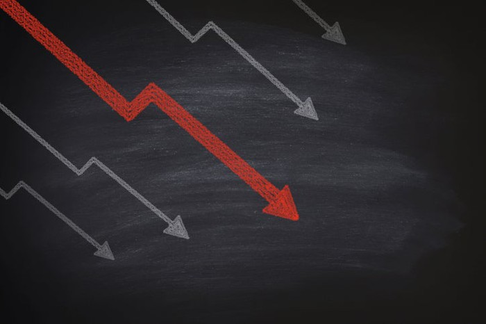 Declining arrows, one red, on a chalkboard.