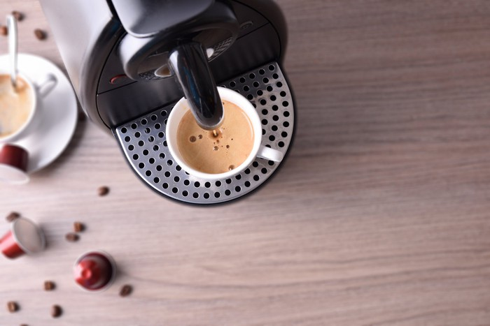 A coffee pod machine brewing a single serving of coffee.