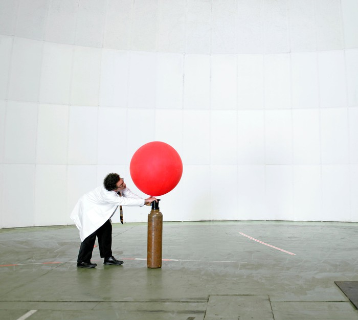 Man inflating balloon with helium.