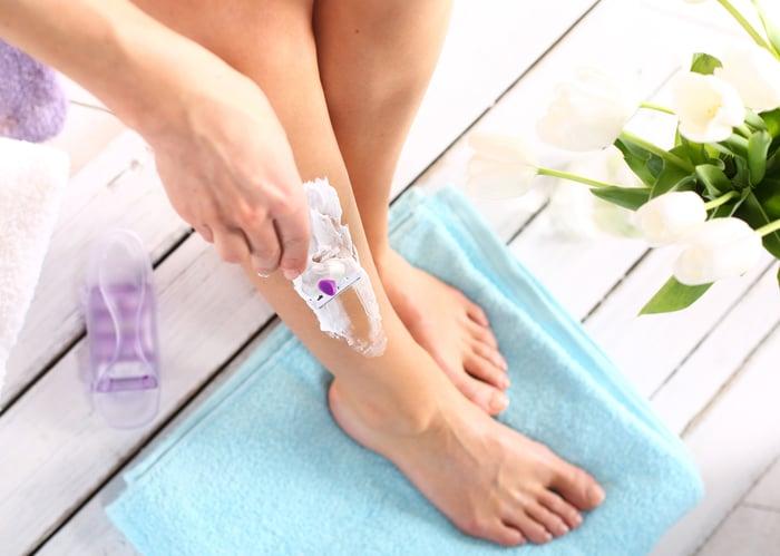 Woman shaving her leg.