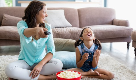 Kid watching TV with mom and popcorn
