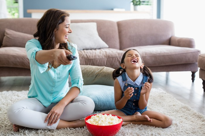 Mother and daughter sharing a bowl of popcorn in front of the TV. Both are smiling and laughing.