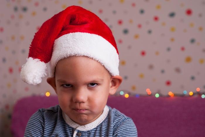 Frowning child wearing Santa elf hat.