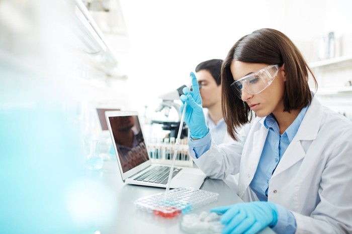 Female scientist with a pipette sitting next to a male scientist who's looking into a microscope.