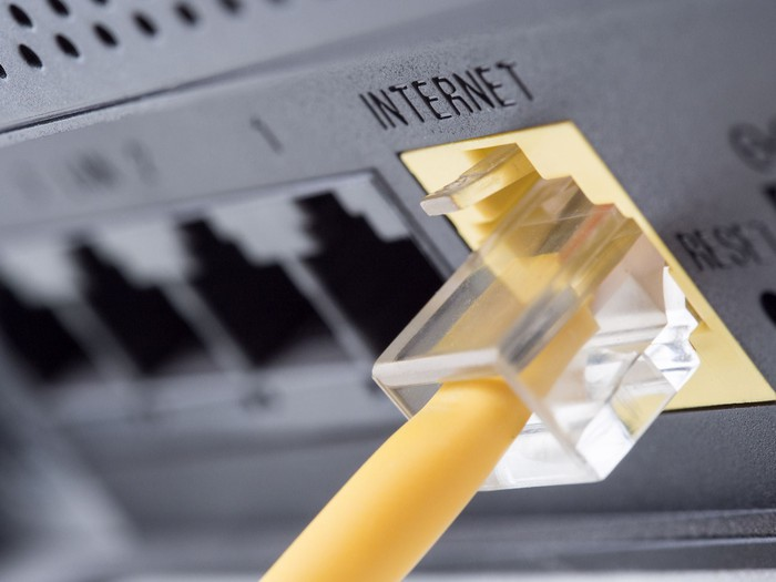 The back of an internet modem with a yellow ethernet cable plugged into it.