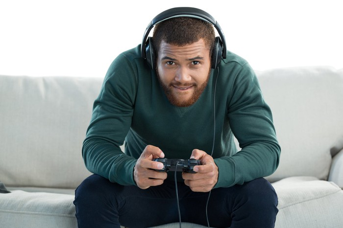 Man in green sweater and black pants sitting on a white couch. He's leaning into the TV screen, wearing headphones and wielding a video game controller.