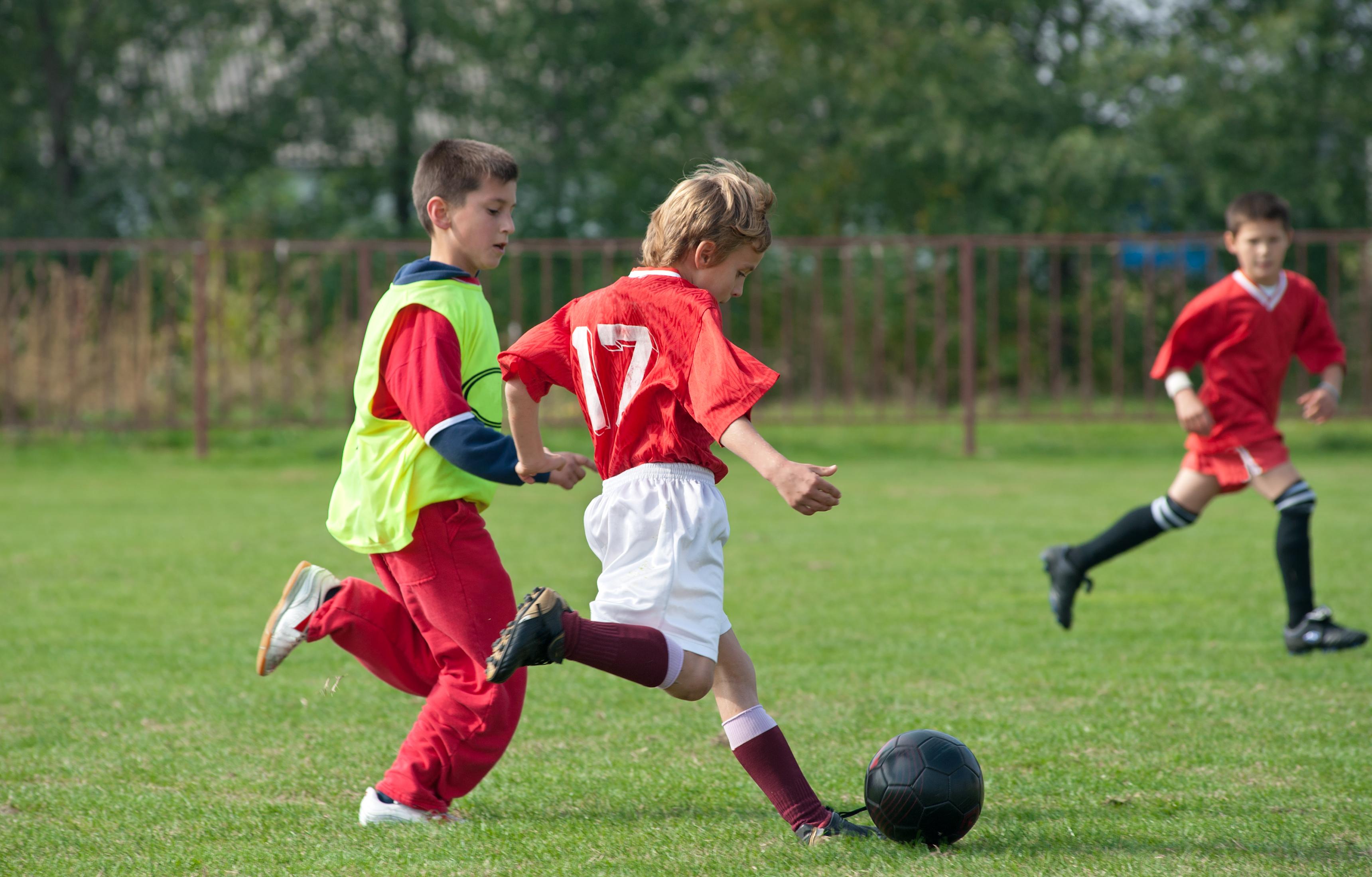 Three boys in uniform playing soccer on a field.