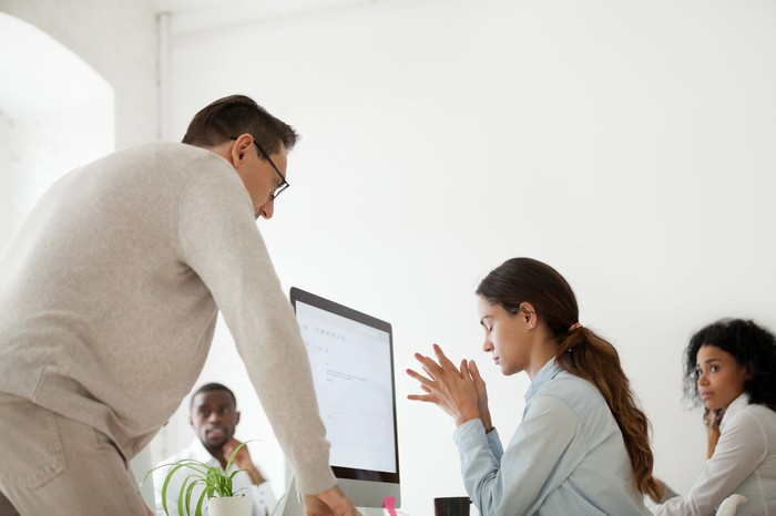 Man stands over a woman at a computer who has her eyes closed, as another man and woman look on.