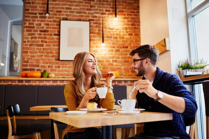 Young couple dining out in cafe; woman is holding a mug and man is holding a spoon above a mug