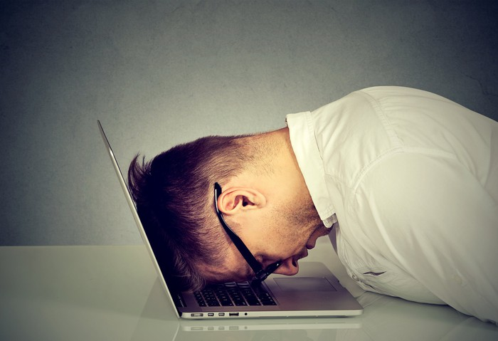 A man with his head resting on a laptop on a desk