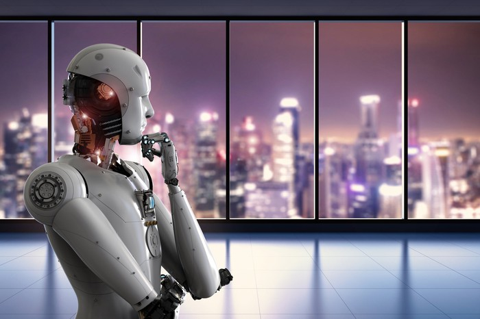 A robot looks out the window of a skyscraper.