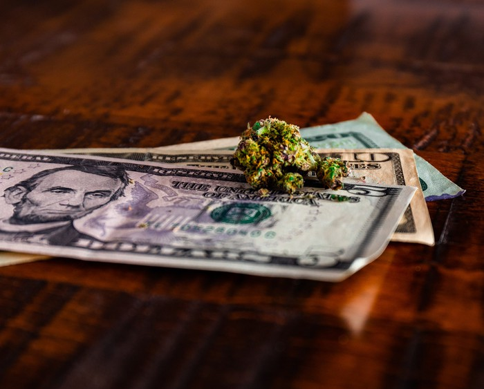 A cannabis bud sits atop a small pile of U.S. currency.