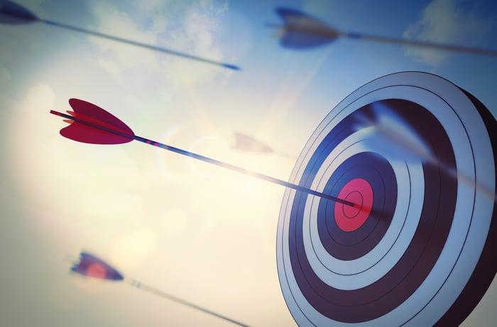 An arrow hits the bull's-eye of a target.