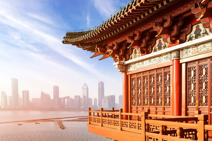 Close-up view of a traditional Chinese building with the skyline of a modern metropolis in the hazy distance.