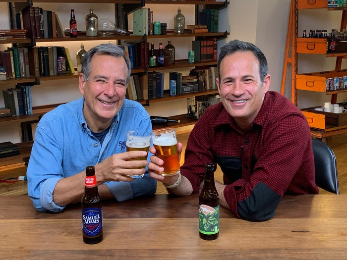 Jim Koch of Boston Beer and Sam Calagione of Dogfish Head sitting at a table and holding their flagship beers.