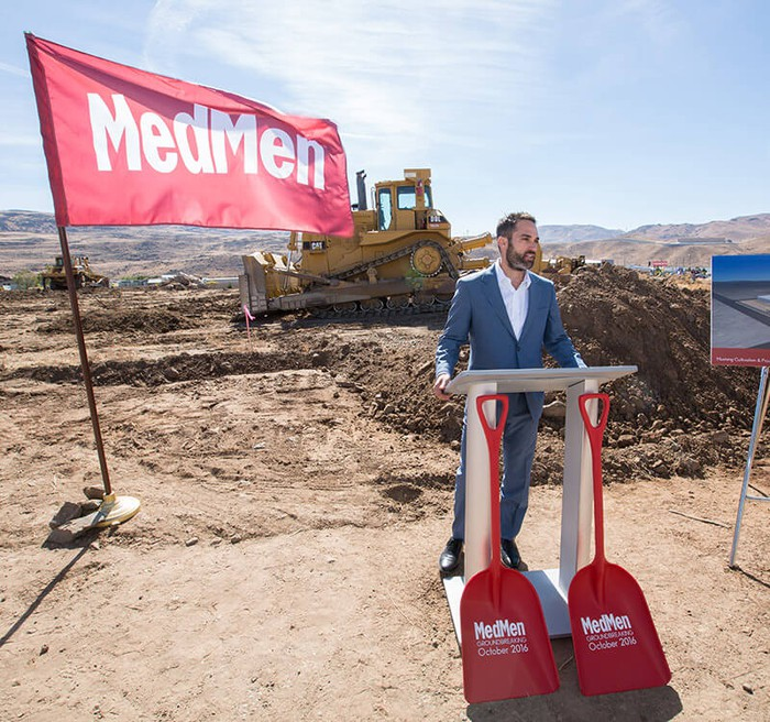 MedMen CEO Adam Bierman speaks at a podium in front of a construction site next to a MedMen flag.