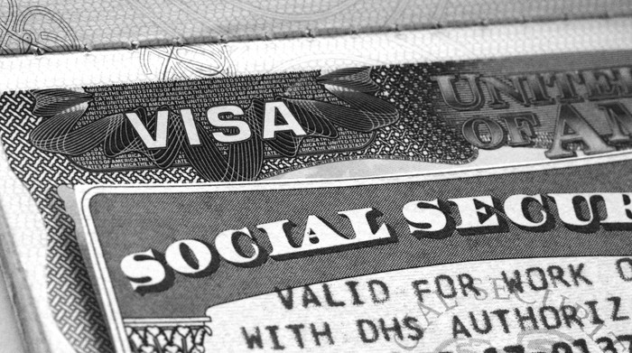 A Social Security card lying atop a work visa.