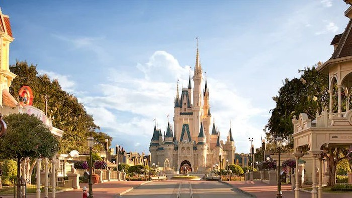 Cinderella's Castle and surrounding area at a Disney domestic theme park with blue sky in background.