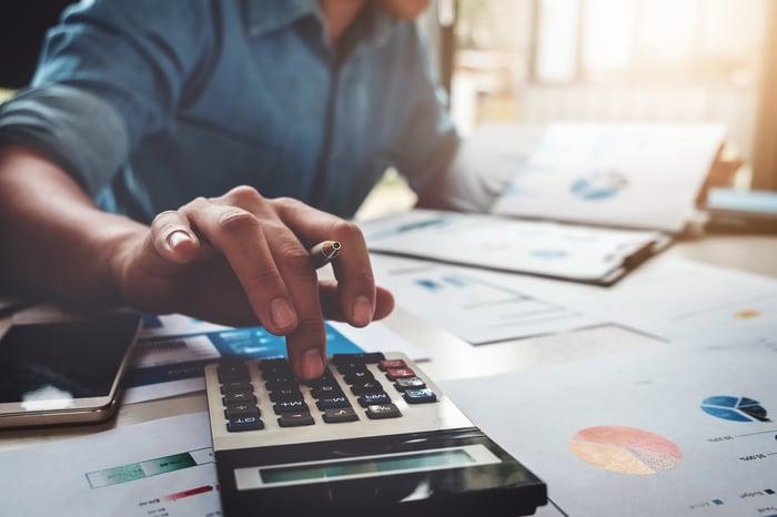 Un homme examine des documents financiers tout en utilisant une calculatrice.