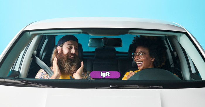 A smiling female Lyft driver in a car with a delighted bearded passenger.