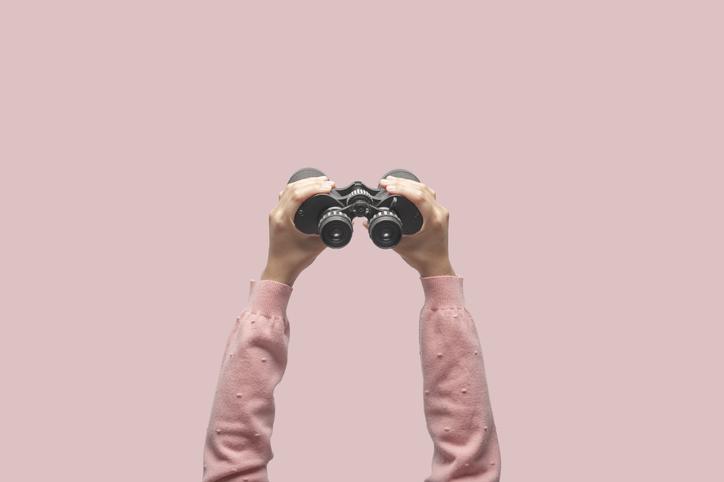 Hands holding up binoculars.