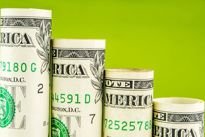 Rolled-up dollar bills arranged in descending order on a green background