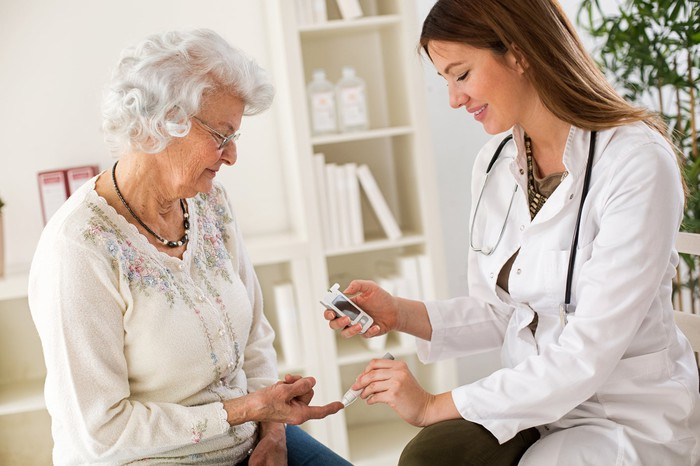 A female doctor testing the blood sugar level of an elderly female patient.