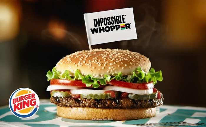 Hamburger with flag reading Impossible Whopper sticking out the top, on a table, with Burger King logo next to it.