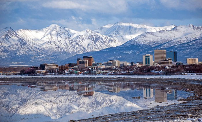 A view of Anchorage, Alaska, with snowcapped mountains in the background.