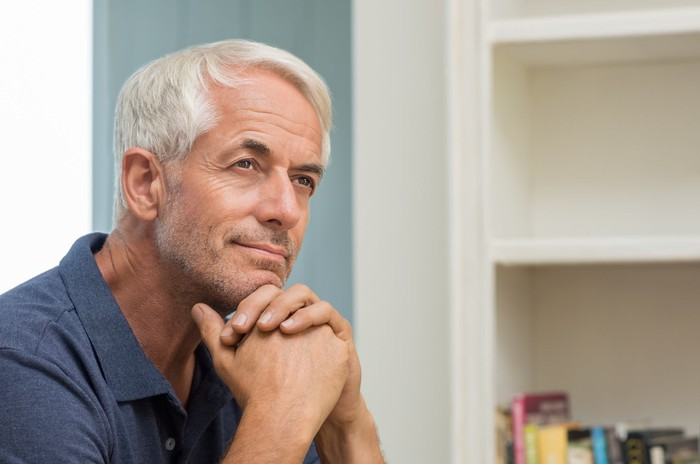 An older man resting his head against his clasped hands, deep in thought