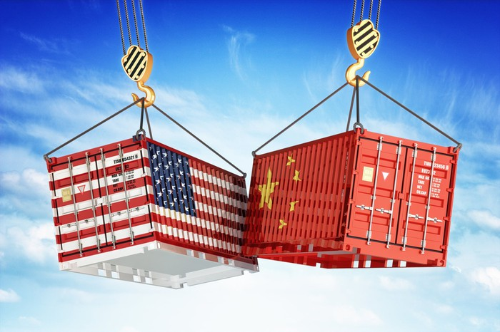 Two shipping containers hanging in midair, one painted with U.S. flag and the other with the Chinese flag.