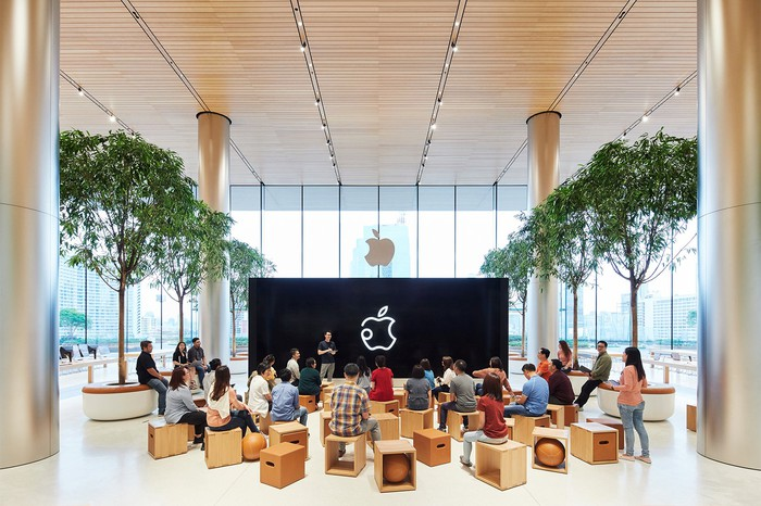 Group of about 20 people sitting on stools in a building with trees, columns, and Apple logos on windows and a screen.