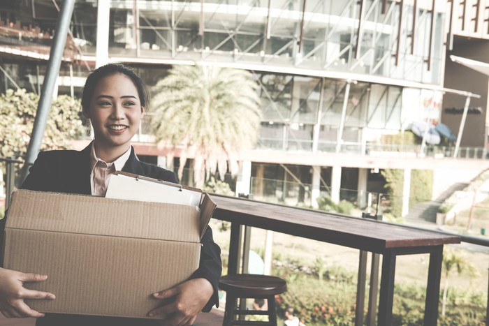Smiling woman in suit outdoors holding cardboard box