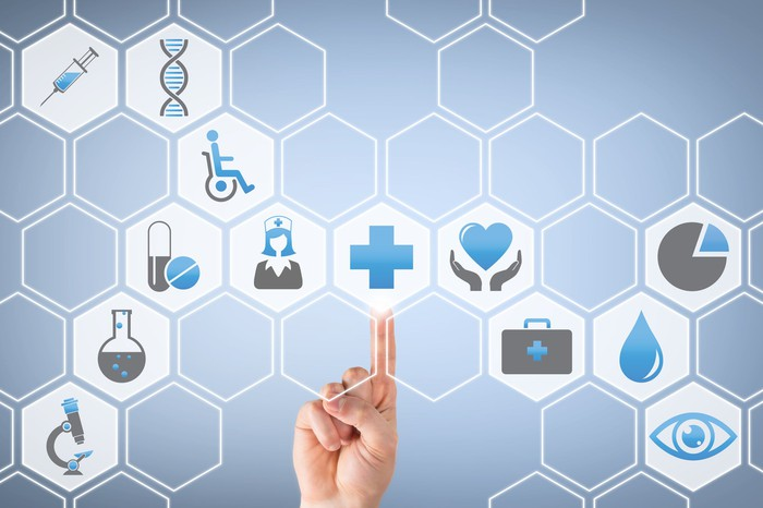 Finger pointing to blue cross in the midst of multiple healthcare-related icons